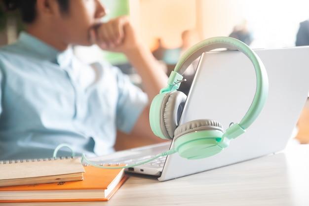 Pastellfarbkopfhörer, laptop-computer und notizbücher auf arbeitsplatzschreibtisch mit gutaussehendem mann.