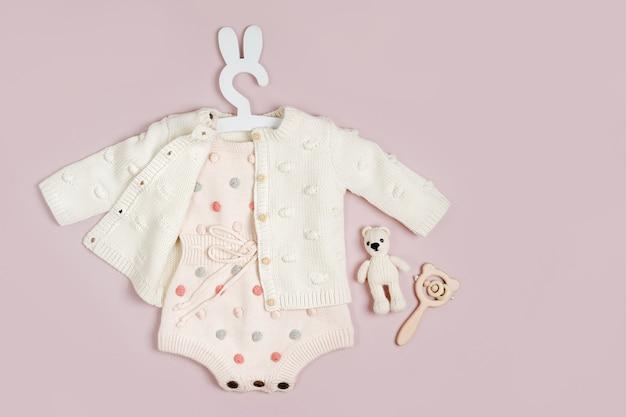 Pastellgestrickter strampler mit pullover, babyschuhen und schnuller. süßes set babykleidung