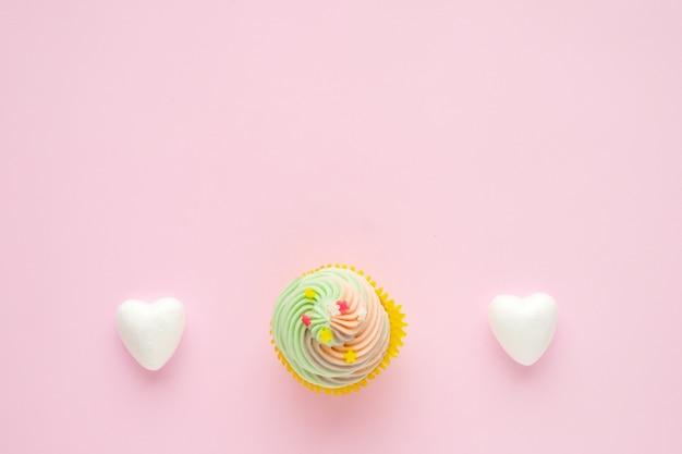 Pastellkleiner kuchen und weiße herzen auf rosa hintergrund mit kopienraum für text