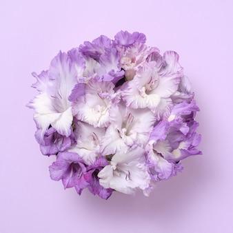 Pastellkreativer moderner strauß aus gladiolenblüten in form eines kreises. kunstvolles einladungsplakat