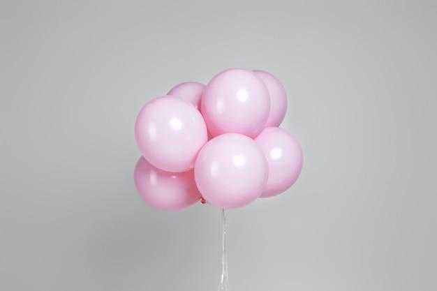 Pastellrosa geburtstagsballons auf grau