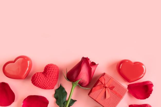 Pastellrosa hintergrund mit roten herzen, geschenken und rose.