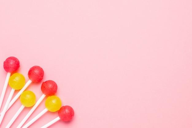 Pastellrosa mit süßem lutscher der rosa und gelben süßigkeiten. minimalistische komposition.