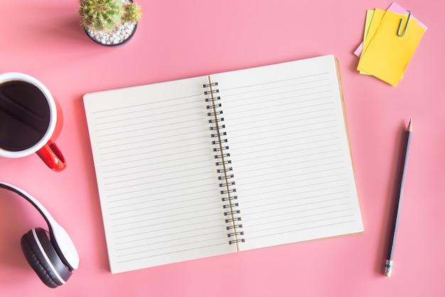 Pastellrosa schreibtisch-büroansicht mit kopierraum für die eingabe des textes.