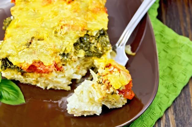 Pastete aus kartoffeln, käse, tomaten und spinat, gefülltes ei mit milch in einem teller auf einer grünen serviette auf einem holzbrett