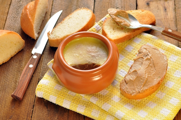 Pastete in einem keramiktopf und toastbrot auf einer serviette. löffel und messer auf hölzernem hintergrund