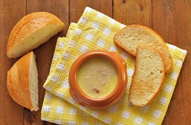 Pastete mit butter in einem keramiktopf und toastbrot auf textilserviette