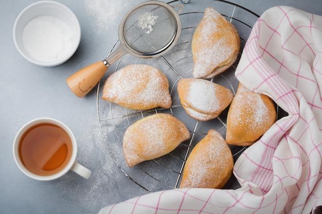 Pasteten mit hüttenkäse und puderzucker auf einer grauen stein- oder betonoberfläche