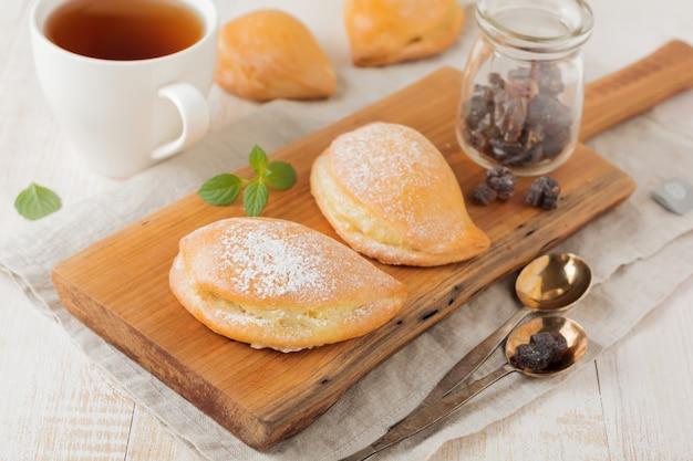 Pasteten mit hüttenkäse und puderzucker auf einer hellen holzoberfläche. traditionelles russisches gebäck sochnik. selektiver fokus