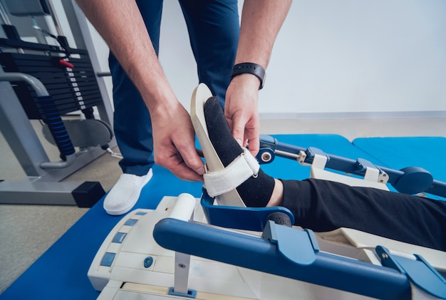 Patient auf cpm-geräten (continuous passive range of motion). gerät zur anatomisch korrekten bewegung des sprunggelenks und der subtalargelenke.