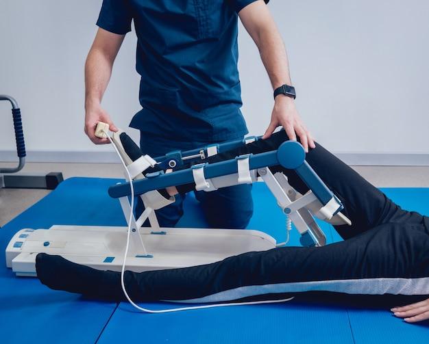 Patient auf cpm-geräten. gerät zur anatomisch korrekten bewegung des sprunggelenks und der subtalargelenke.
