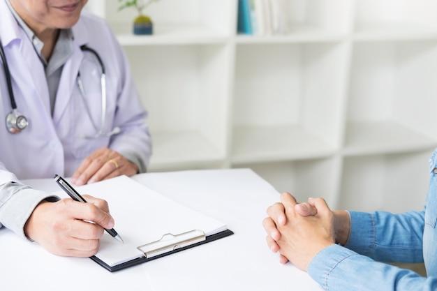 Patient, der aufmerksam auf einen männlichen arzt hört, der patientensymptome erklärt oder eine frage stellt, während sie in einer konsultation den papierkram besprechen