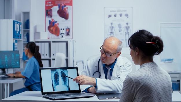 Patient, der beim arzttermin saubere lungen hat und die ergebnisse mit dem arzt bespricht. ältere erfahrene ärztin im gespräch mit patienten über lunge, röntgenpneumonie, krebs, untersuchungsspezialist