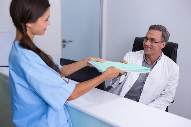 Patient, der dem zahnarzt akten gibt