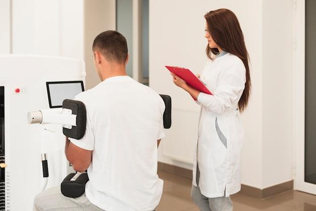 Patient der hinteren ansicht, der das medizinische gerät überwacht vom doktor verwendet