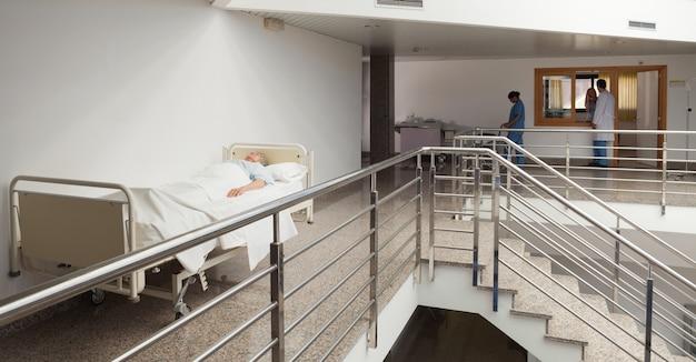Patient, der im bett im ruhigen korridor liegt