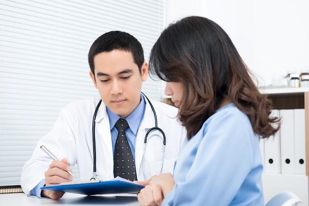 Patient der jungen frau, der mit asiatischem männlichem doktor sich berät