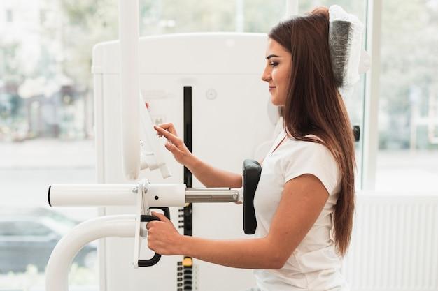 Patient der seitlichen ansicht, der medizinische trainingsmaschine verwendet