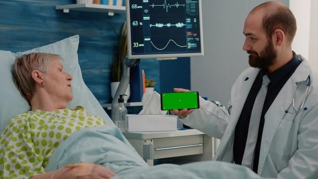 Patient im ruhestand, der auf dem telefon auf den horizontalen grünen bildschirm schaut