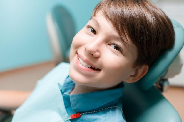 Patient im zahnarztstuhl. teen boy, der zahnbehandlung bei zahnarztpraxis hat.