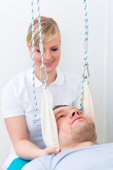 Patient in der physiotherapie macht mit seinem therapeuten in der praxis körperliche übungen auf dem schlingentisch