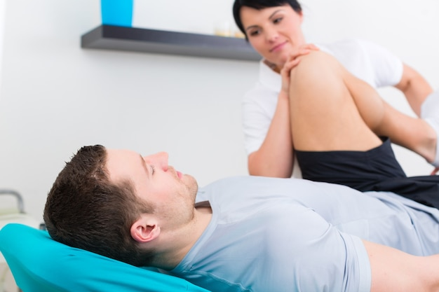 Patient in der physiotherapie macht mit seinem therapeuten körperliche übungen