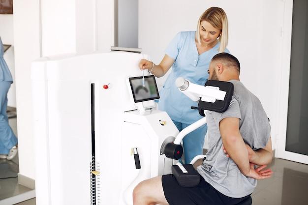Patient macht sport mit sportgeräten mit therapeuten