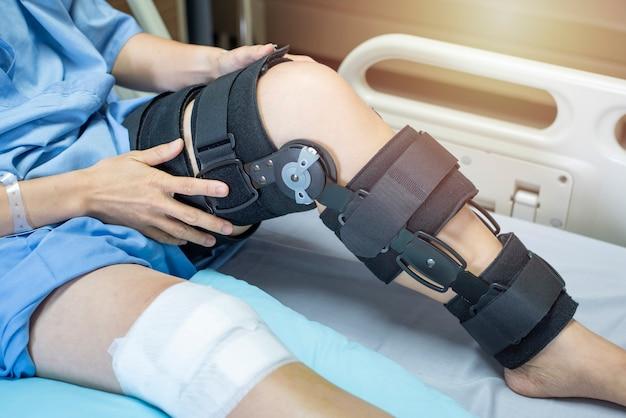 Patient mit bandage kompressionsknieorthese stützverletzung auf dem bett im pflegeheim. gesundheitswesen und medizinische unterstützung.