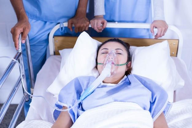 Patient mit der sauerstoffmaske, die auf bett und doktoren stehen nahe dem bett liegt