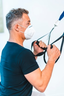 Patient mit maske macht armübungen. wiedereröffnung mit sicherheitsmaßnahmen von physiotherapeuten bei der covid-19-pandemie. osteopathie, therapeutische chiromassage