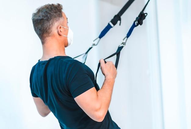 Patient mit maske und schwarzem t-shirt macht armübungen. wiedereröffnung mit sicherheitsmaßnahmen von physiotherapeuten bei der covid-19-pandemie. osteopathie, therapeutische chiromassage