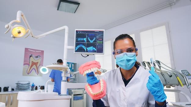 Patient pov des zahnarztes, der frau die korrekte reinigung der zähne in der zahnarztpraxis mit skelettzubehör beibringt. stomatolog trägt schutzmaske und bittet um präsentationszähne medizinisches objekt