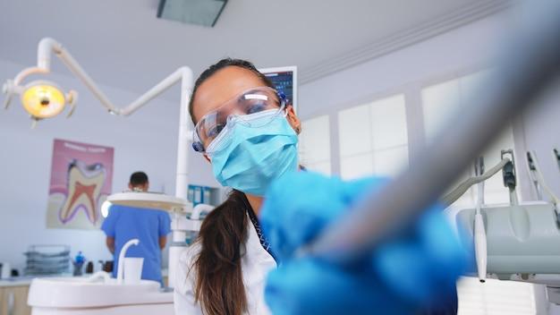 Patient pov zum arzt im stomatologischen büro, das die zähne der frau behandelt. kieferorthopädischer spezialist und mannassistent, der in einer modernen zahnklinik mit masken und handschuhen arbeitet.