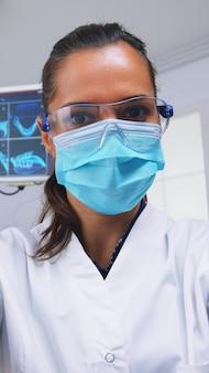 Patient pov zum stomatologen, der untersuchungen durchführt und zähne mit zahnärztlichen werkzeugen in einer modernen klinik pflegt. arzt und krankenschwester, die in einem modernen kieferorthopädischen büro arbeiten und eine schutzmaske tragen