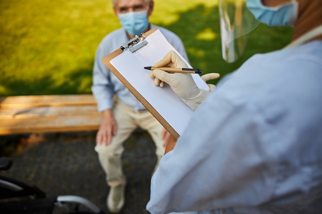 Patient sitzt auf der bank, während der arzt notizen schreibt