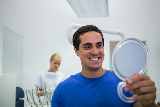 Patient überprüft seine zähne im spiegel