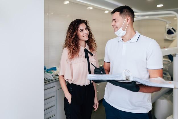Patient und zahnarzt, die einander im büro betrachten