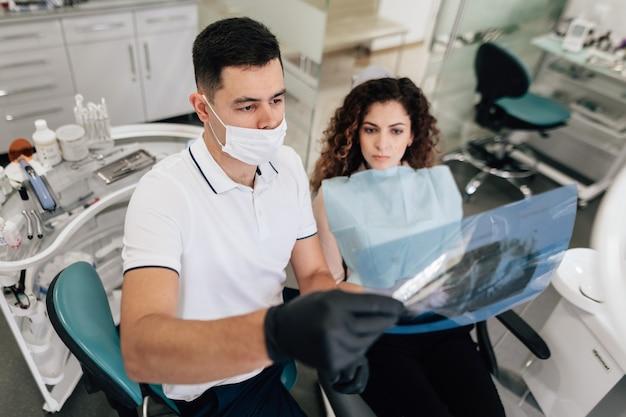 Patient und zahnarzt, die radiographie betrachten