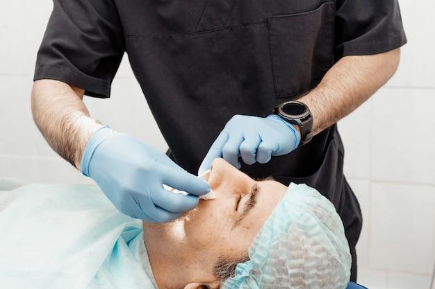 Patient und zahnarzt während der implantatinsertion. echte bedienung. zahnextraktion, implantate. berufsuniform und ausrüstung eines zahnarztes. gesundheitswesen ausstattung eines arztarbeitsplatzes. zahnheilkunde