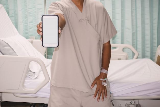 Patient zeigt den monitor des smartphones im krankenhaus