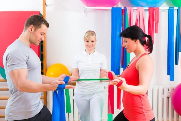 Patienten in der physiotherapie machen körperliche übungen mit dem therapeuten