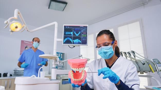 Patienten-pov des zahnarztes, der die korrekte art der reinigung der zähne zeigt, die in der zahnarztpraxis mit medizinischem skelettzubehör der zähne getragen werden. stomatolog trägt schutzmaske beim gesundheitscheck