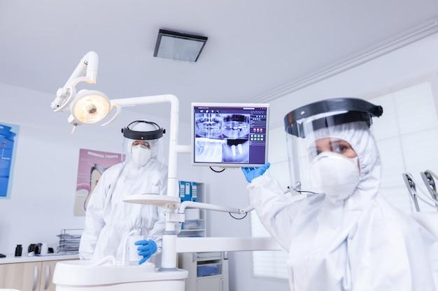 Patienten-pov des zahnarztes mit gesichtsschutz, der die zahnärztliche röntgenaufnahme erklärt, die auf den monitor zeigt. facharzt für stomatologie, der einen schutzanzug gegen eine infektion mit coronavirus trägt, der auf die radiographie zeigt.