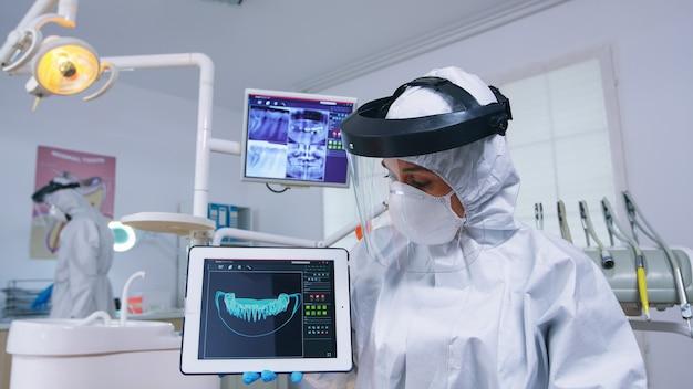 Patienten-pov-hörexplikation für die zahnbehandlung, zahnarzt im overall, der röntgen auf tablet zeigt. facharzt für stomatologie, der schutzanzug gegen infektion mit covid19 trägt und auf röntgenbild zeigt