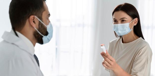 Patienten und arzt sprechen mit medizinischen masken