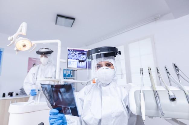 Patientenansicht aus erster person des zahnarztes, der kieferradiographie hält und über zahnbehandlung spricht. zahnmediziner, der einen schutzanzug gegen coroanvirus trägt, der radiographie zeigt.