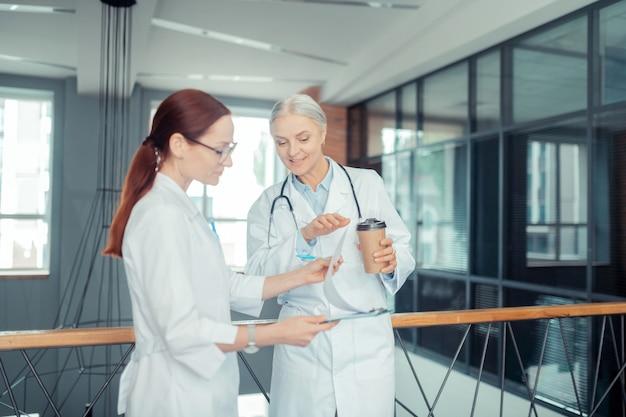 Patientenkarte. zwei zufriedene ärztinnen betrachten eine zwischenablage mit einer patientenkarte, während sie im flur stehen