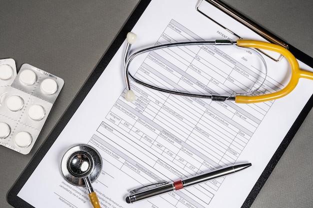 Patientenprofil und stethoskop auf dem tisch. der arzt zeichnet die ergebnisse der blutuntersuchung des patienten auf