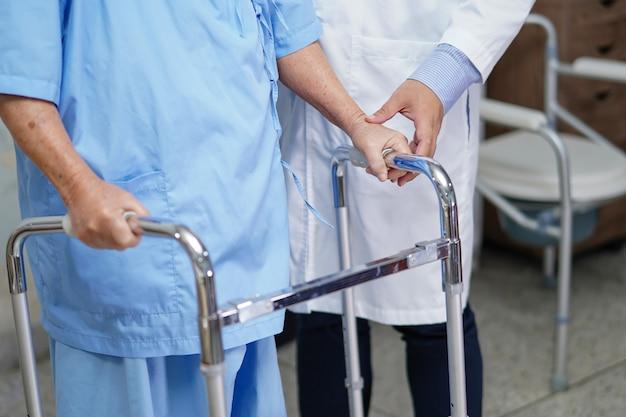 Patientenweg der asiatischen älteren frau der doktorhilfe mit wanderer am krankenhaus.