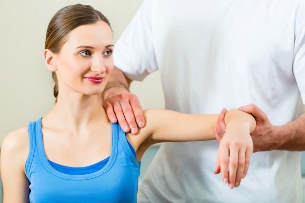 Patientin bei der physiotherapie, die mit ihrem therapeuten körperliche übungen macht, gibt ihr eine medizinische massage